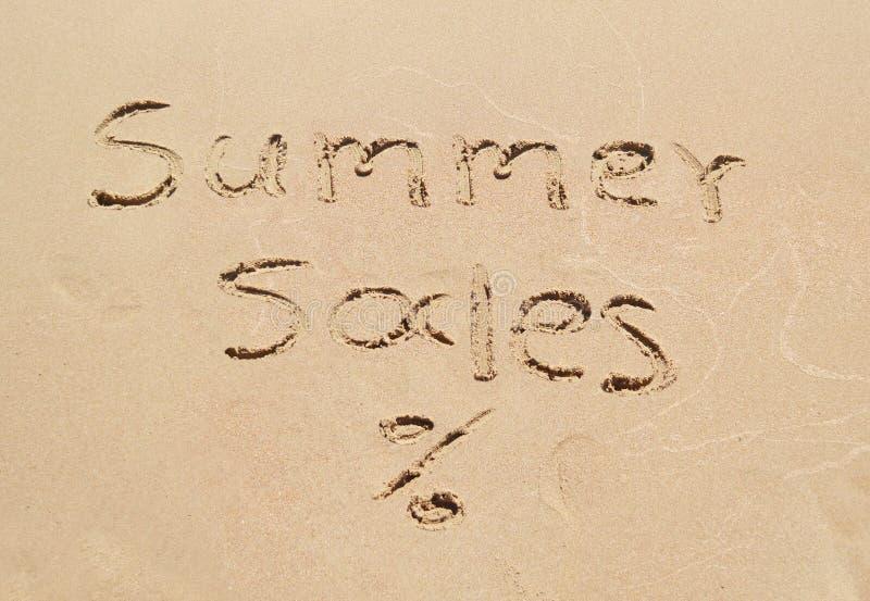 Vendas escritas na areia - compra sazonal do verão do disconto foto de stock