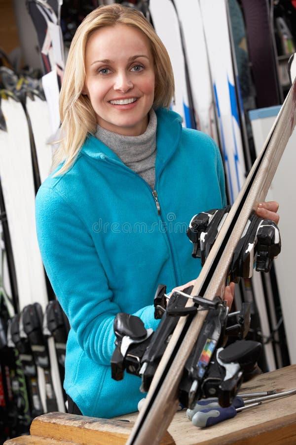 Vendas fêmeas assistentes com os esquis na loja do aluguer imagens de stock royalty free