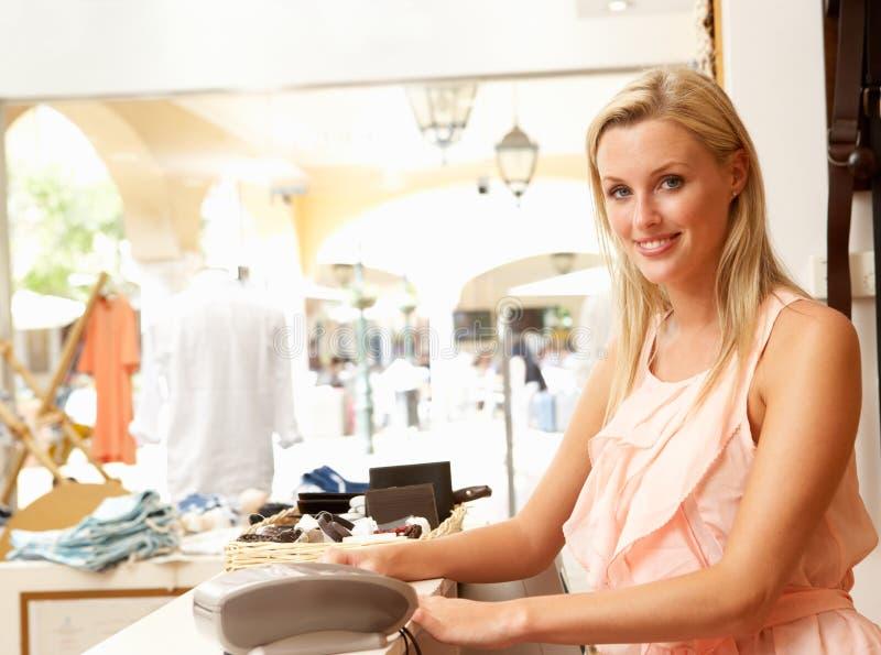 Vendas fêmeas assistentes na loja de roupa imagem de stock