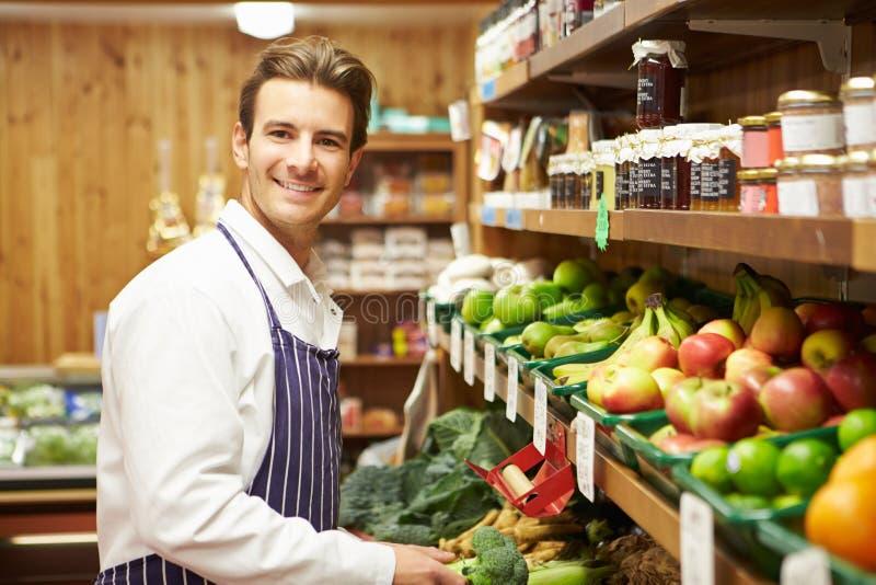 Vendas masculinas assistentes no contador vegetal da loja da exploração agrícola fotografia de stock