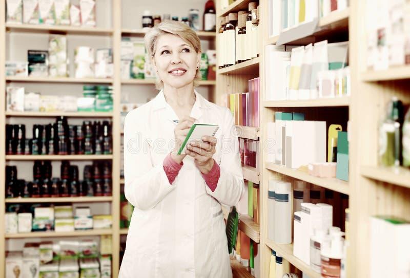 Vendedor agradable de la mujer que anota productos del cuidado en tienda fotos de archivo