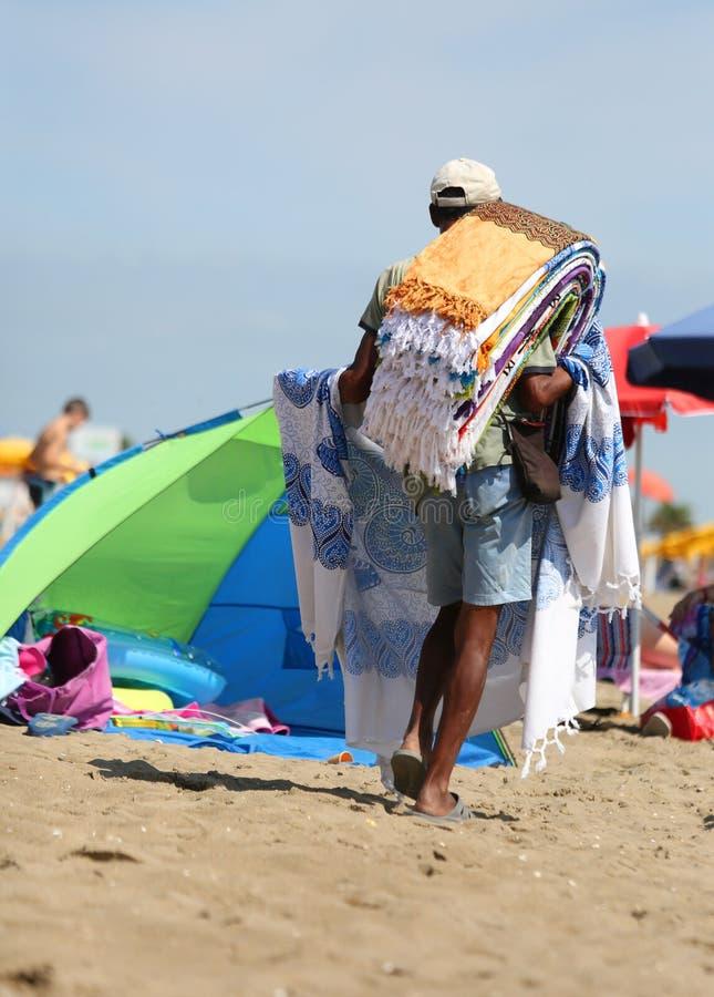 vendedor ambulante abusivo en la arena mientras que vende las toallas y ser imagen de archivo libre de regalías