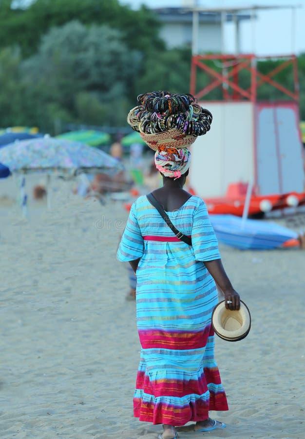 Vendedor ambulante africano de la mujer de collares y de pulseras en la playa imagenes de archivo
