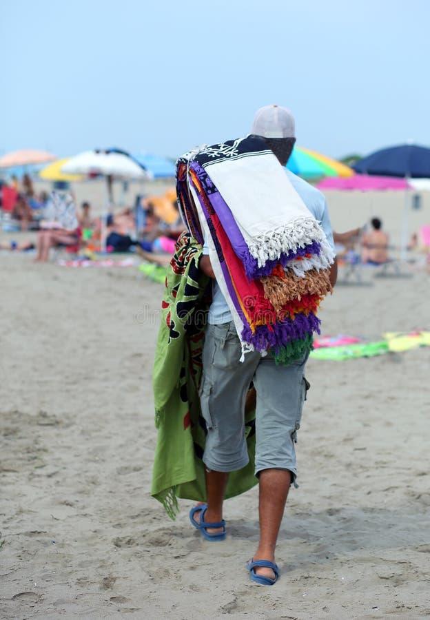 Vendedor ambulante de toallas coloridas por el mar en la playa fotografía de archivo libre de regalías