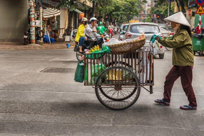Vendedor ambulante em Hanoi, Vietname que cruza a estrada fotografia de stock