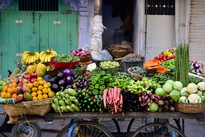 Vendedor ambulante indiano com legumes frescos e frutos imagem de stock