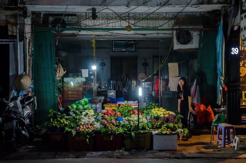 Vendedor ambulante no identificado que vende las frutas al lado de la calle en Hanoi, Vietnam imagen de archivo