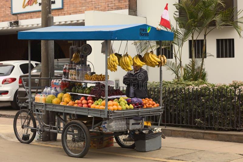 Vendedor ambulante no identificado que vende las frutas de un carro foto de archivo libre de regalías