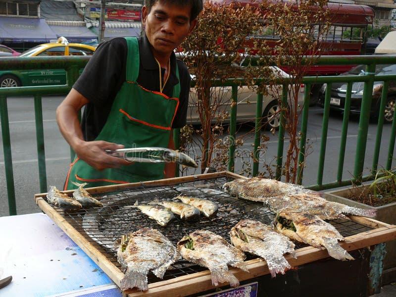 Vendedor ambulante que cocina pescados en Bangkok Tailandia imagen de archivo