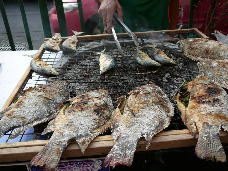Vendedor ambulante que cocina pescados en las calles de Bangkok Tailandia fotos de archivo