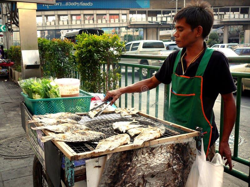 Vendedor ambulante que cocina pescados en las calles de Bangkok Tailandia fotografía de archivo libre de regalías