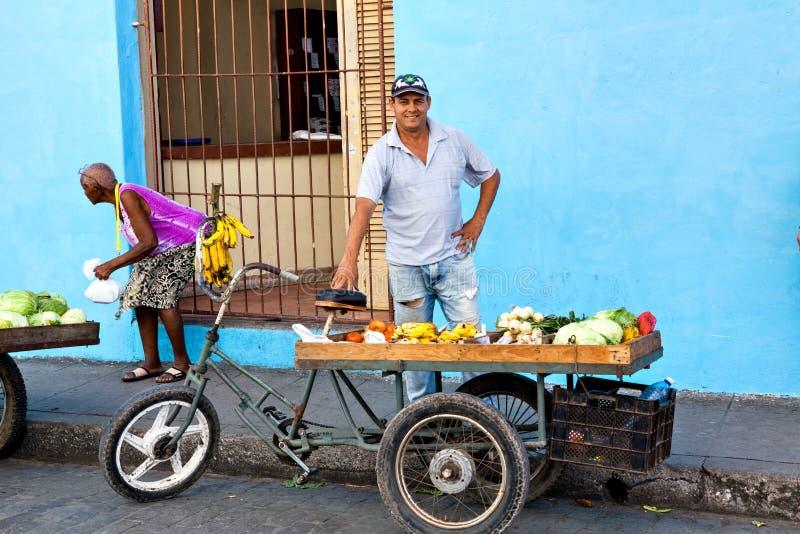 Vendedor ambulante que vende frutas e legumes em sua bicicleta nas ruas de Camaguey, Cuba foto de stock