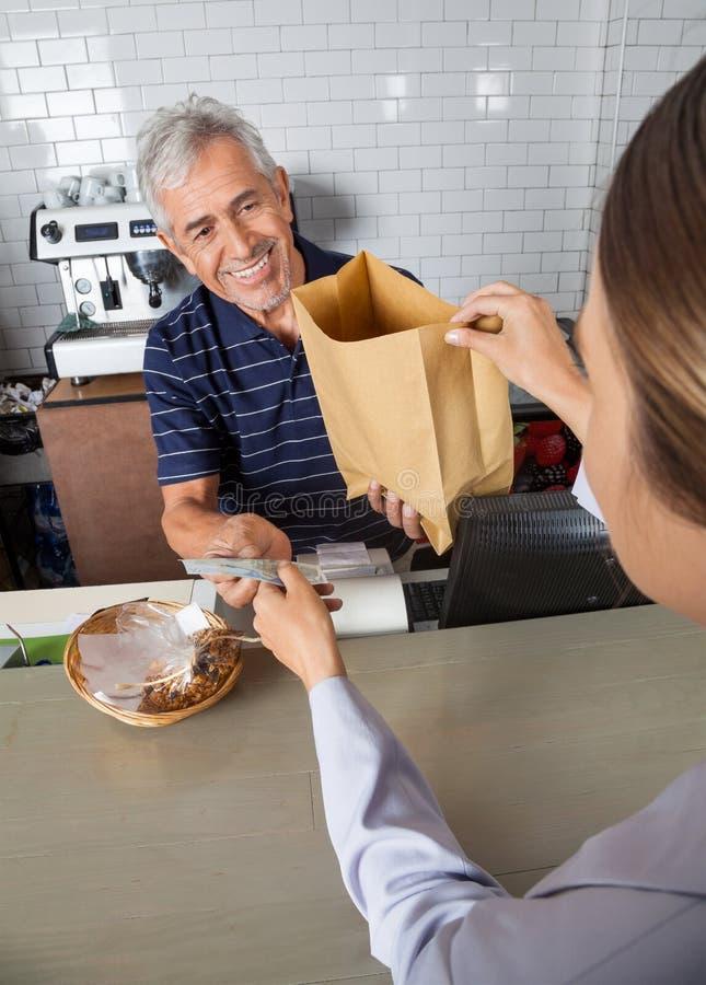 Vendedor Collecting Cash While que passa o saco de mantimento fotografia de stock royalty free