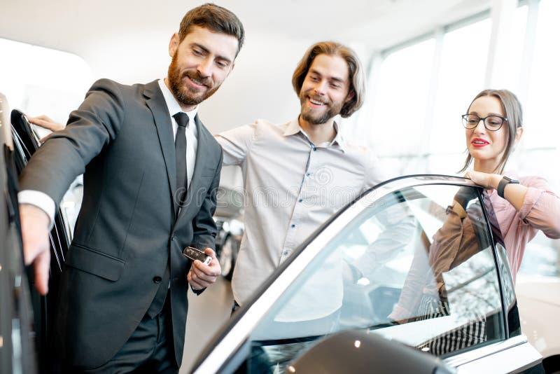 Vendedor com pares na sala de exposições do carro imagem de stock royalty free