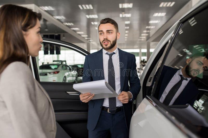 Vendedor considerável Selling Cars na sala de exposições foto de stock royalty free