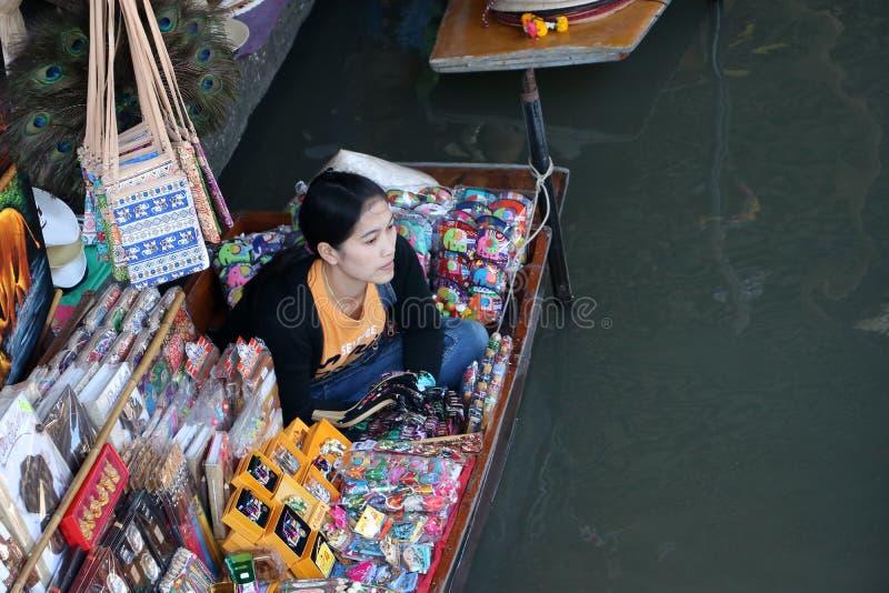 Vendedor da lembrança que senta-se em seu barco no canal no mercado de flutuação de Damnoen Saduak imagem de stock