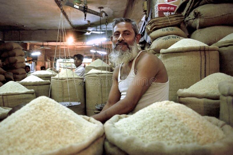 Vendedor de Bangladesh del arroz en la parada en mercado interior imágenes de archivo libres de regalías