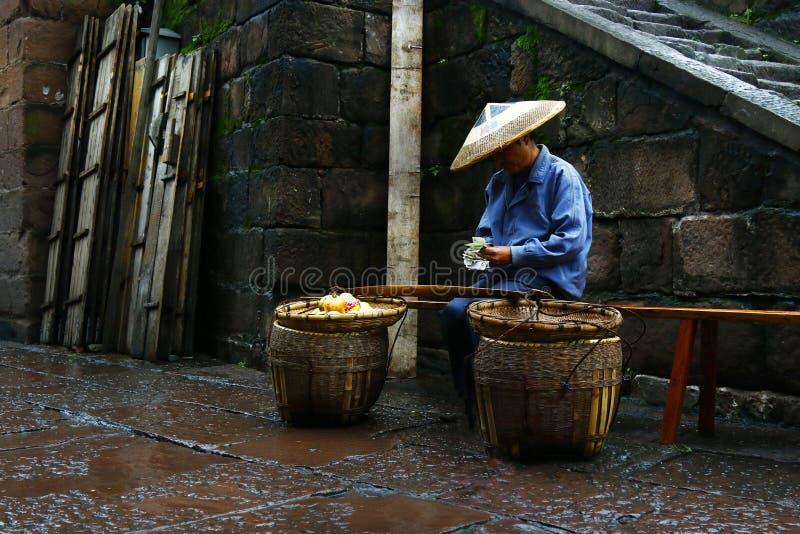 VENDEDOR DE CALLE, VENDIENDO LA FRUTA EN MERCADO fotografía de archivo libre de regalías