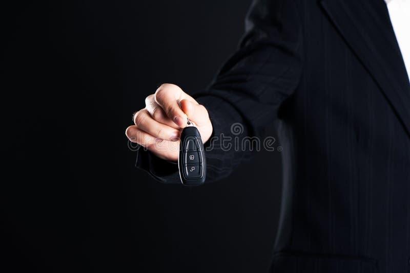Vendedor de carro que cede seus chaves, negócio e venda novos do carro fotografia de stock