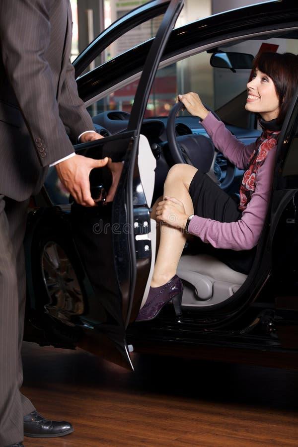 Vendedor de carro que dá as chaves do carro a uma jovem mulher imagem de stock