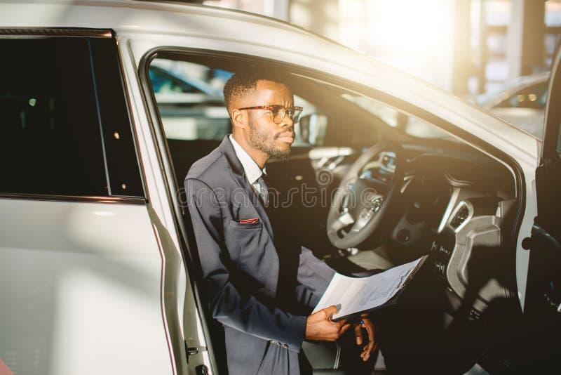 Vendedor de coches africano hermoso que se coloca en la representación que sostiene una tableta foto de archivo libre de regalías