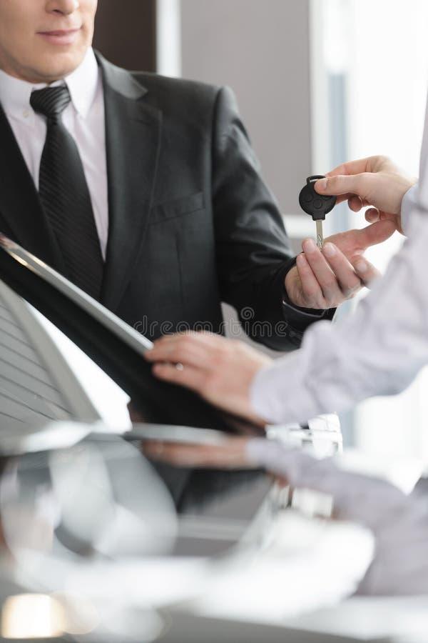 Vendedor de coches que da la llave al nuevo owne del coche fotografía de archivo