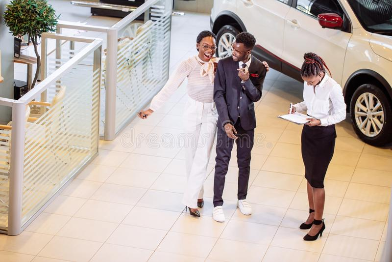 Vendedor de coches que se coloca en la representación que habla de características del coche a los clientes fotos de archivo libres de regalías