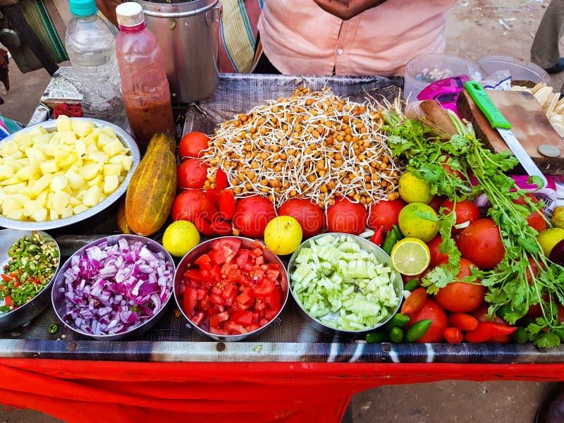 Vendedor de comida indio de la calle que vende la mezcla picante del chole del gramo adornada con la cebolla, los chiles del pepi foto de archivo