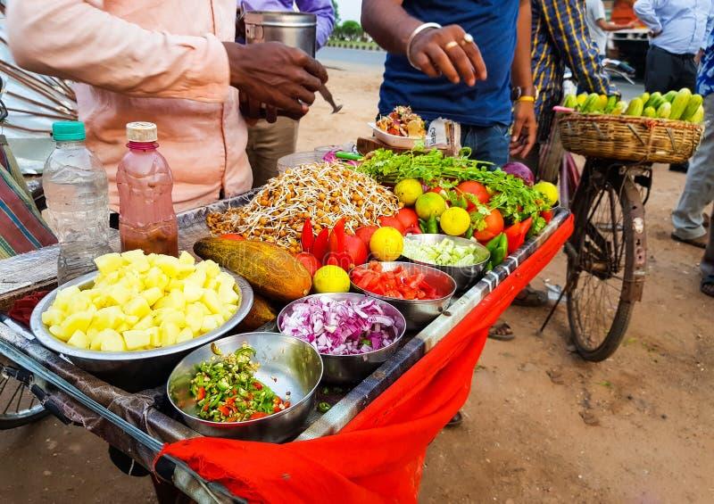 Vendedor de comida indio de la calle que vende la mezcla picante del chole del gramo adornada con la cebolla, los chiles del pepi foto de archivo libre de regalías