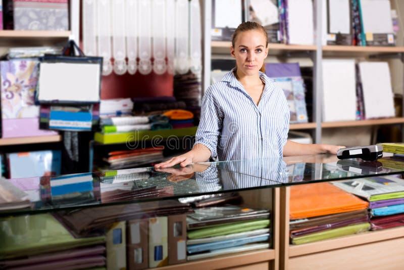 Vendedor de la mujer que mira útil el contador imágenes de archivo libres de regalías