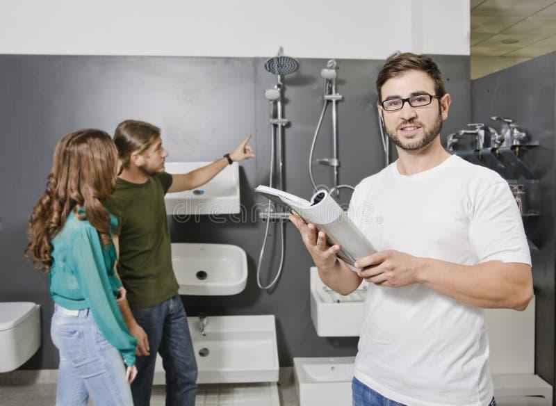 Vendedor de las ventas que mira el catálogo la tienda de la fontanería imagen de archivo libre de regalías
