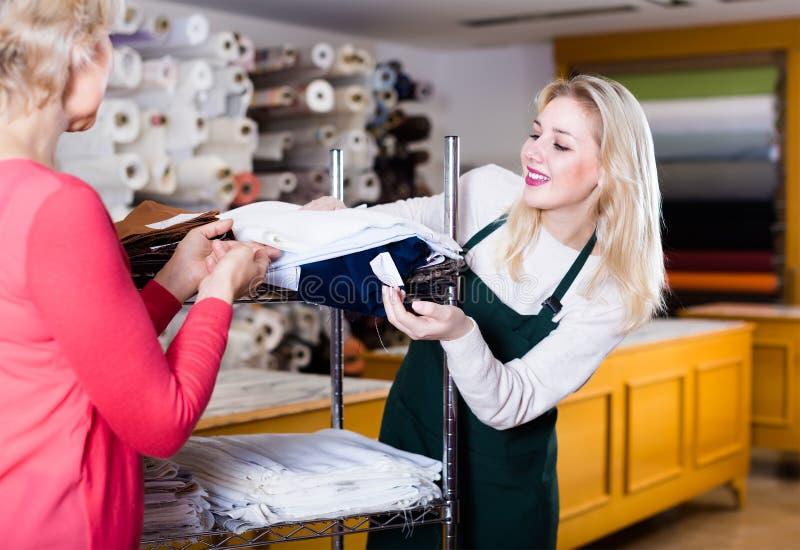 Vendedor de sexo femenino atento que demuestra telas al comprador mayor adentro fotografía de archivo