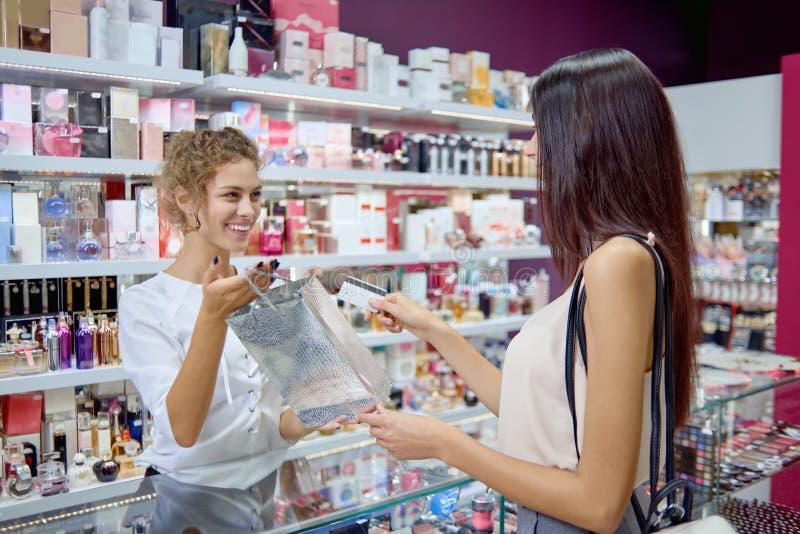 Vendedor de sexo femenino positivo que da al cliente de la compra en tienda de los cosméticos fotos de archivo