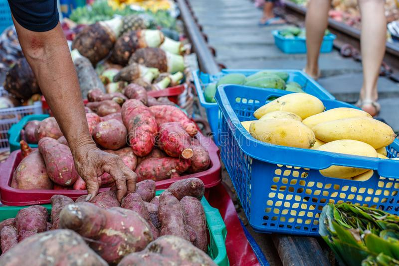 Vendedor de sexo femenino que comprueba las patatas dulces en un mercado ferroviario famoso de Maeklong, provincia de Samut Songk fotografía de archivo