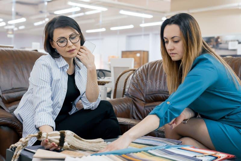 Vendedor de sexo femenino que habla con el comprador en la tienda de telas y de accesorios para las cortinas, sala de exposición  fotografía de archivo