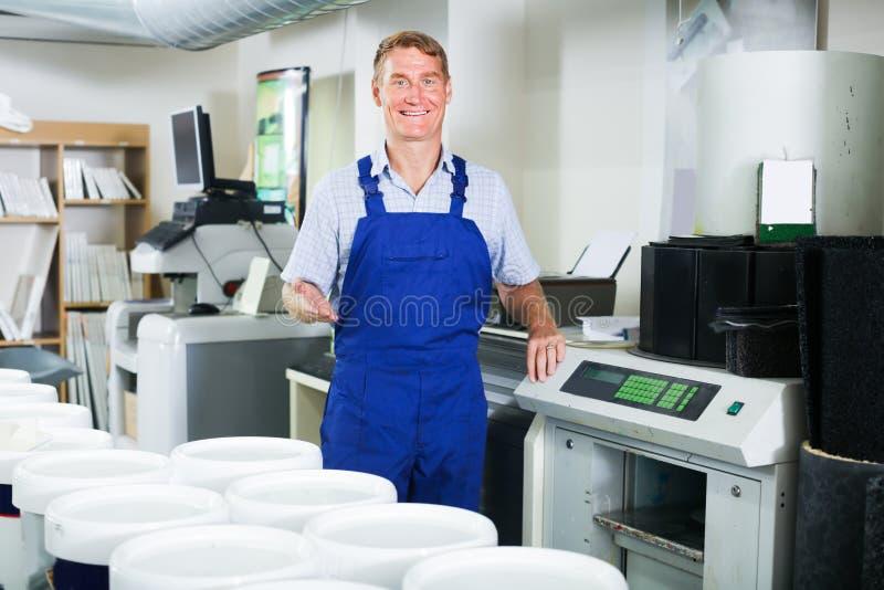 Vendedor de sexo masculino alegre que trabaja con el elevador de las mercancías foto de archivo libre de regalías