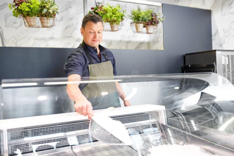 Vendedor de sexo masculino que añade el hielo al refrigerador en el colmado foto de archivo libre de regalías