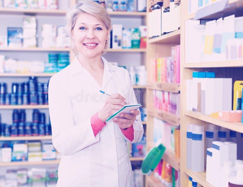 Vendedor de sorriso da mulher que escreve para baixo produtos do cuidado na loja fotografia de stock