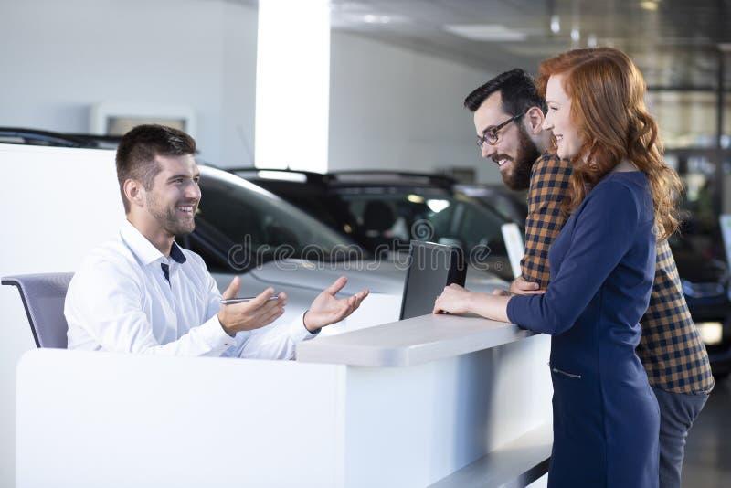 Vendedor de sorriso do carro que fala com os compradores felizes na sala de exposições exclusiva imagens de stock royalty free