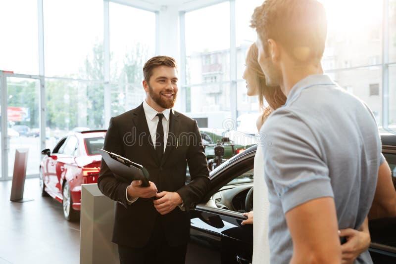 Vendedor de sorriso que mostra o carro novo a um par fotografia de stock royalty free