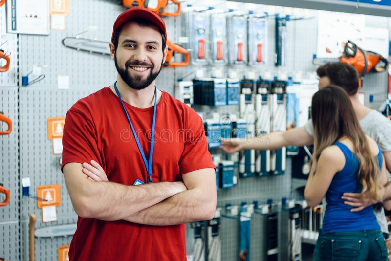 Vendedor de sorriso seguro na loja das ferramentas elétricas O indivíduo está pronto para ajudar clientes foto de stock