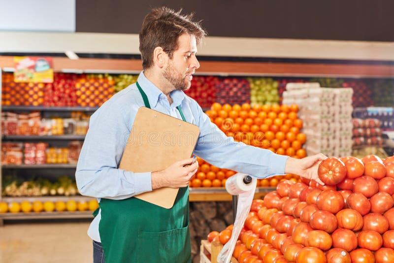 Vendedor de supermercados inspeciona legumes imagens de stock