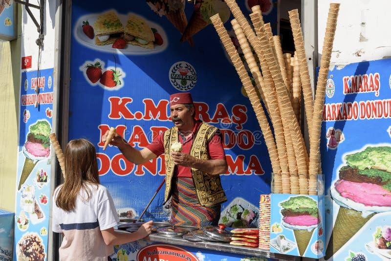 Vendedor del helado, vestido en traje turco tradicional en una tienda de la calle imagenes de archivo