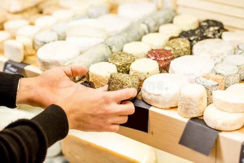Vendedor del queso en la tienda foto de archivo