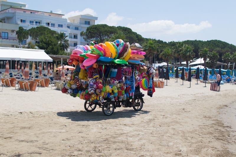 Vendedor desconocido de juguetes inflables y de revestimientos que nadan que montan una bicicleta colgada con los juguetes albani imagenes de archivo