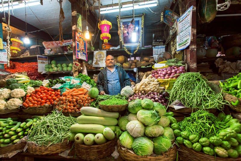 Vendedor do abobrinha, da couve, dos verdes e dos outros vegetais esperando clientes no mercado do fazendeiro fotografia de stock royalty free