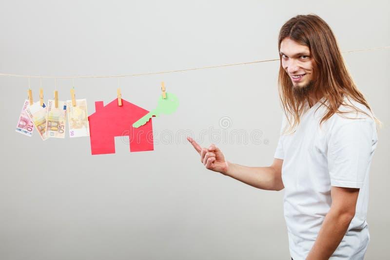 Vendedor do homem com dinheiro e casa foto de stock royalty free