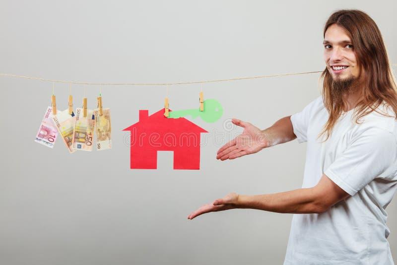 Vendedor do homem com dinheiro e casa imagens de stock