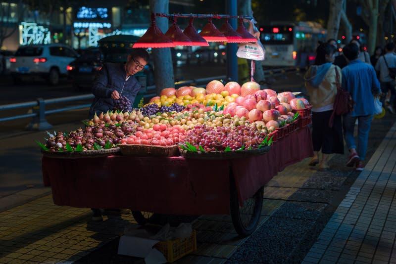Vendedor do mercado de frutos da rua na noite em Chengdu imagem de stock