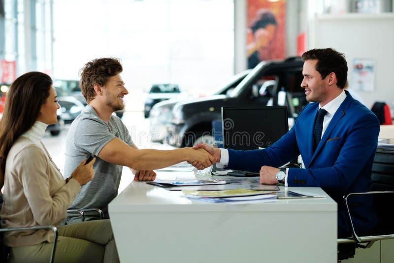 Vendedor e cliente que agitam as mãos que felicitam-se na sala de exposições do negócio imagem de stock